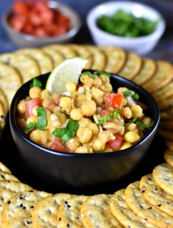 A bowl of white peas dip garnished with onions, tomato, cilantro and a wedge of lime