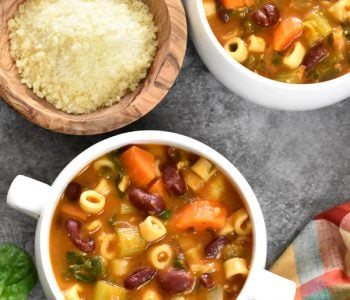 Two white bowls with pasta fagioli soup served with a bowl of grated parmesan cheese