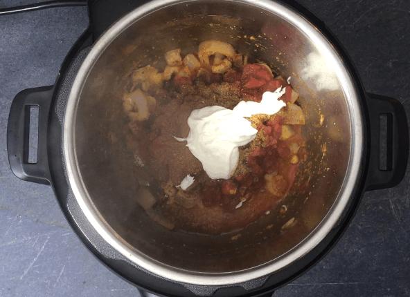 Sautéing tomatoes, spices with yogurt to make Chicken Tikka Masala sauce