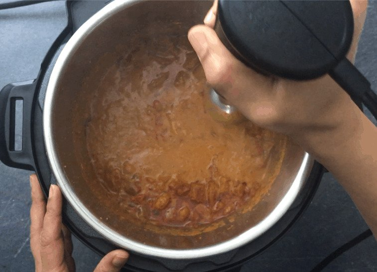 Pureeing the chicken tikka masala sauce with a hand blender
