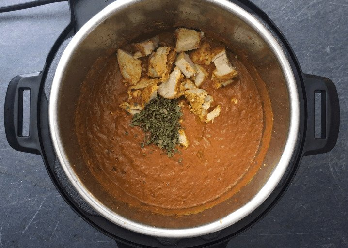 Adding Diced chicken with fenugreek leaves to the tikka masala sauce
