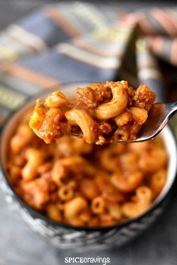 A bite of american goulash in a fork with ground turkey and pasta