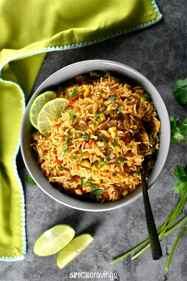Mexican rice with corn and peppers, garnished with lime and cilantro