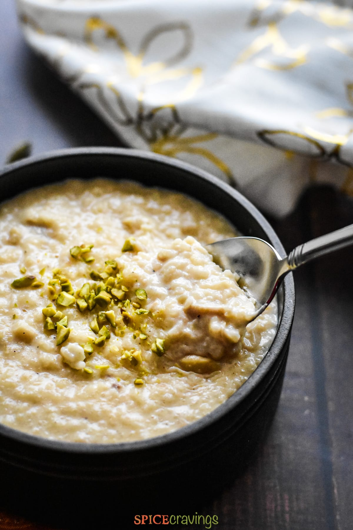Indian rice pudding, kheer, served in a black bowl, garnished with pistachios