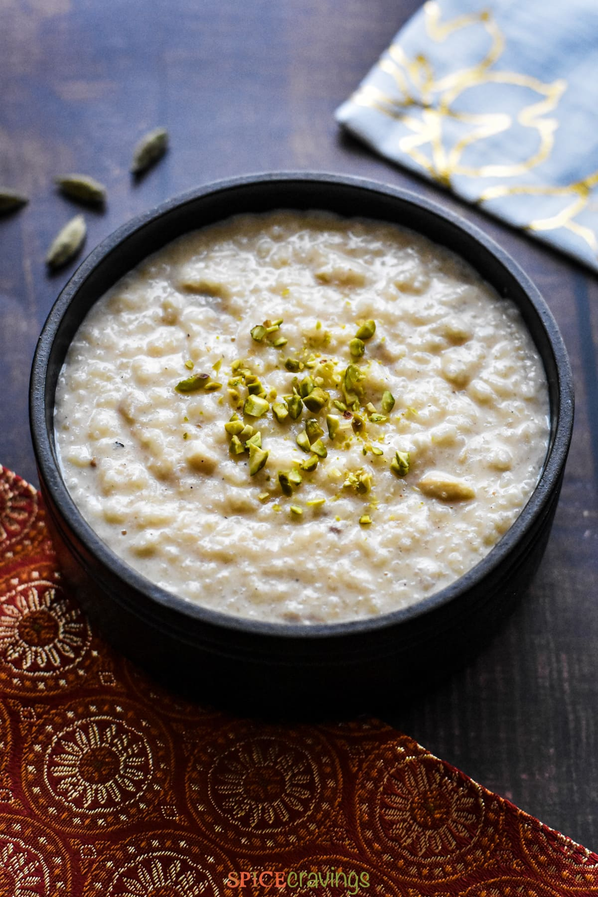 Kheer, Indian rice pudding, served in a black stone bowl, garnished with pistachios