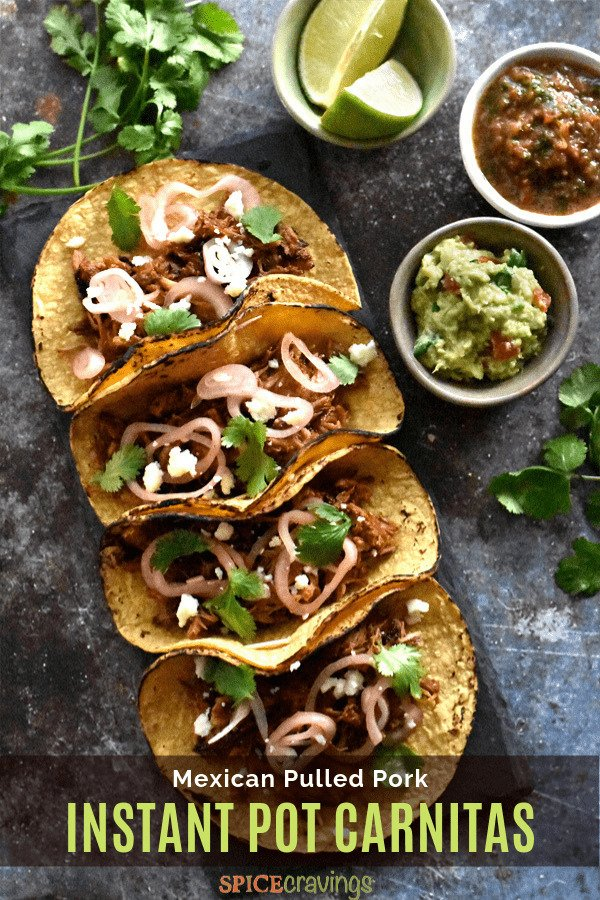 Four corn tortillas filled with crispy carnitas, garnished with onions and cilantro