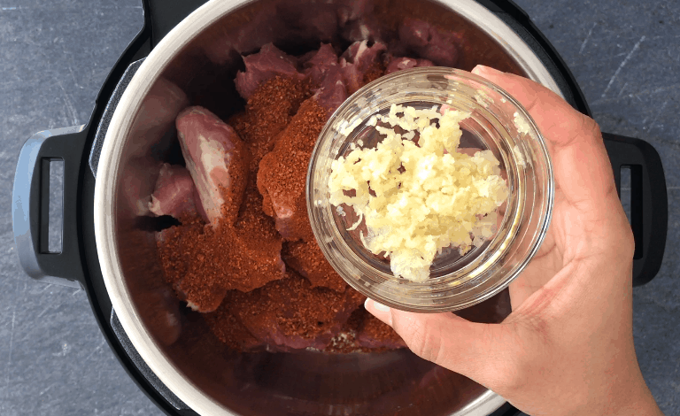 Adding grated garlic to the meat