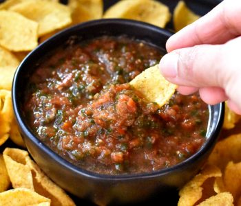 Dipping a corn chip in a bowl of homemade salsa