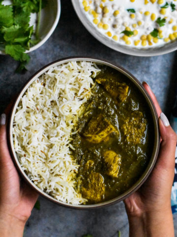A bowl of chicken Saag curry served with basmati rice