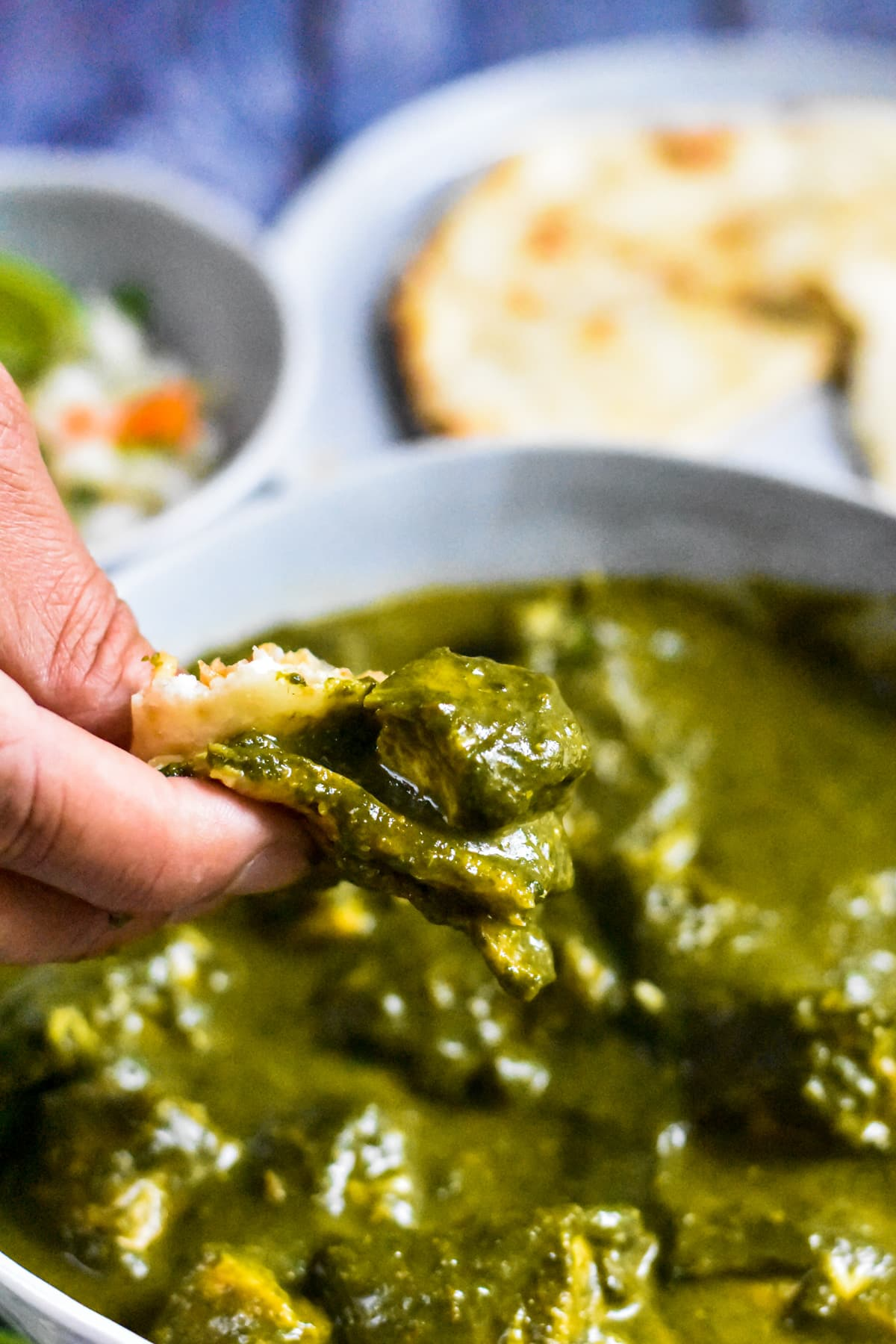 Scooping Chicken Saag with a piece of naan