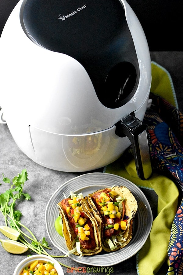 Blackened fish tacos placed next to an Air Fryer