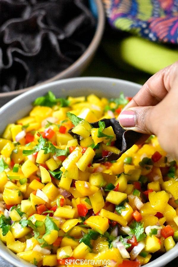 Scooping mango salsa with blue corn tortilla chip