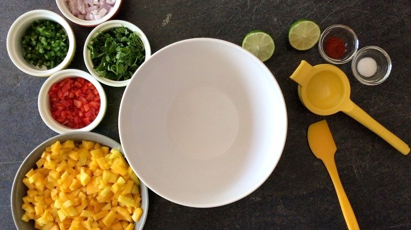 ingredients needed to mango salsa on a cutting board