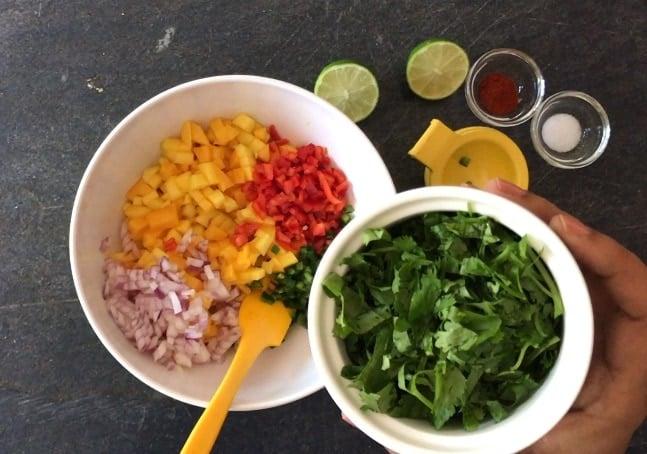 Adding chopped cilantro  to mango, onion and red pepper
