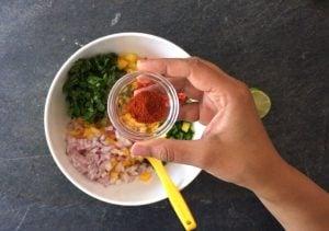 Seasoning the mango salsa ingredients with chili powder