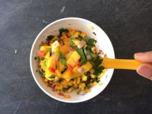 A spoonful of freshly mango salsa with peppers, onion, jalapeno and lime