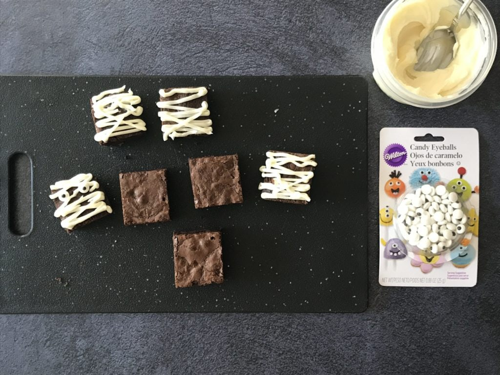 Cream Cheese icing, brownies and candy eyes on a black cutting board