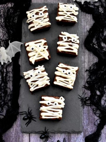 Brownies decorated to look like 'Mummies' placed on a gray slate