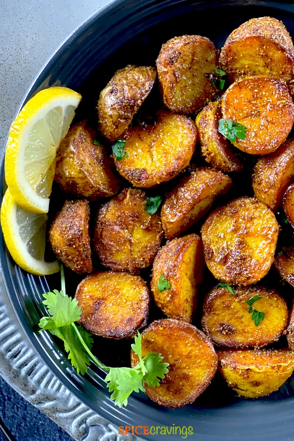 Roasted Bombay Potatoes served in a black bowl with lemon slices