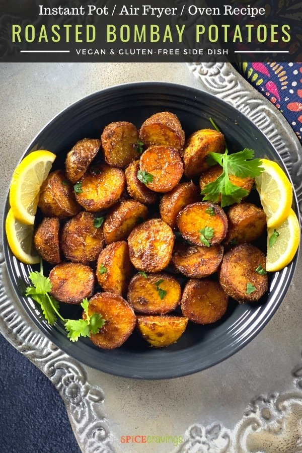 A bowl of roasted bombay spice potatoes garnished with lemon slices and cilantro