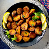 Spicy roasted bombay potatoes served in a black bowl
