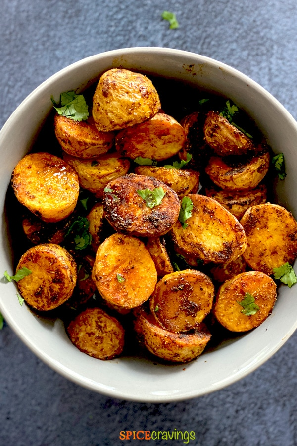 Spicy Bombay Potatoes served with chopped cilantro in a grey bowl