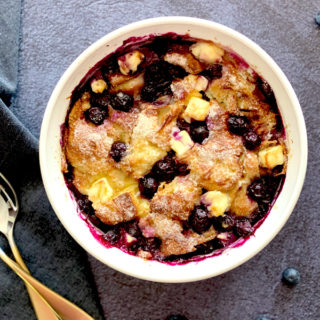 Creamy bread pudding with blueberries in a white bowl