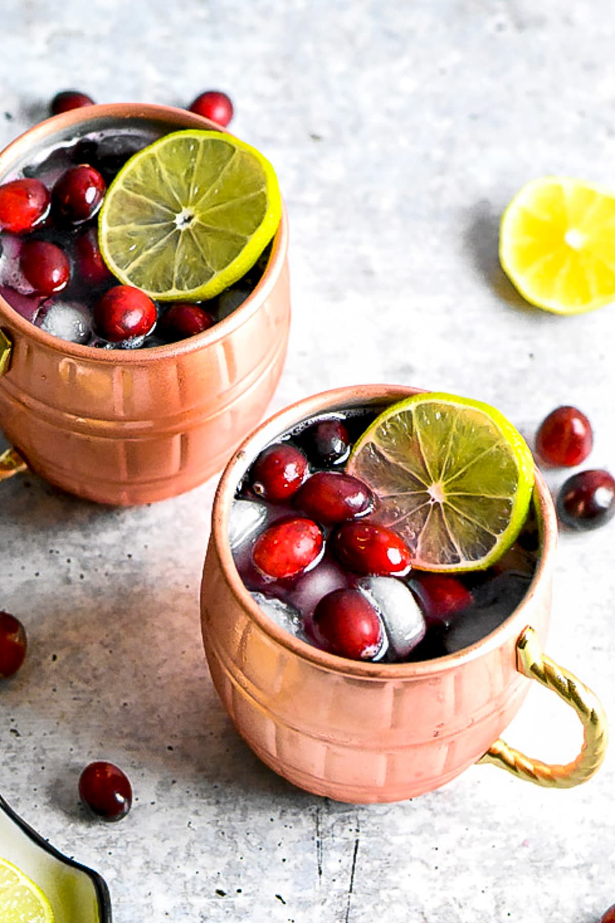 Two copper mugs with Moscow Mule topped with cranberries and lime