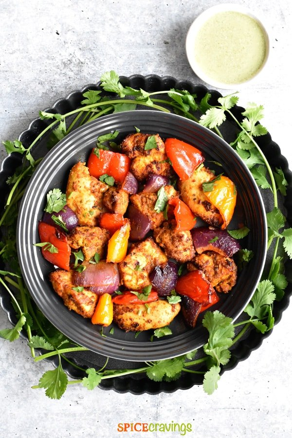 Grilled Chicken Tikka served in a plate decorated with cilantro leaves on the side