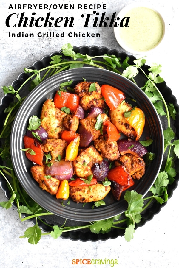 Grilled Chicken and peppers served in a gray plate with cilantro on the side