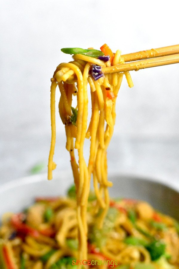 Picking Lo Mein noodles with chopsticks