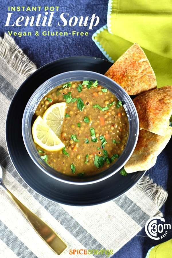 zesty instant pot lentil soup in gray bowl garnished with lemon slices and pita bread on side