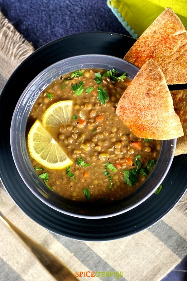 instant pot lentil soup in gray bowl with lemon slices and pita