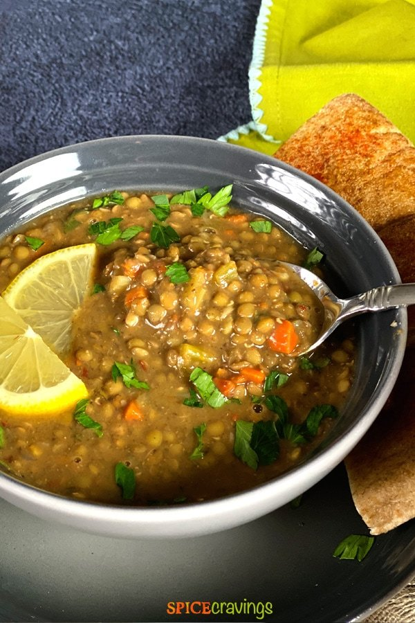 instant pot lentil soup recipe in gray bowl with lemon slices and spoon