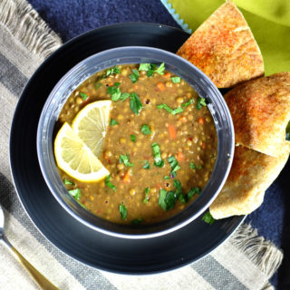 instant pot lentil soup in gray bowl on blue plate with pita on the side