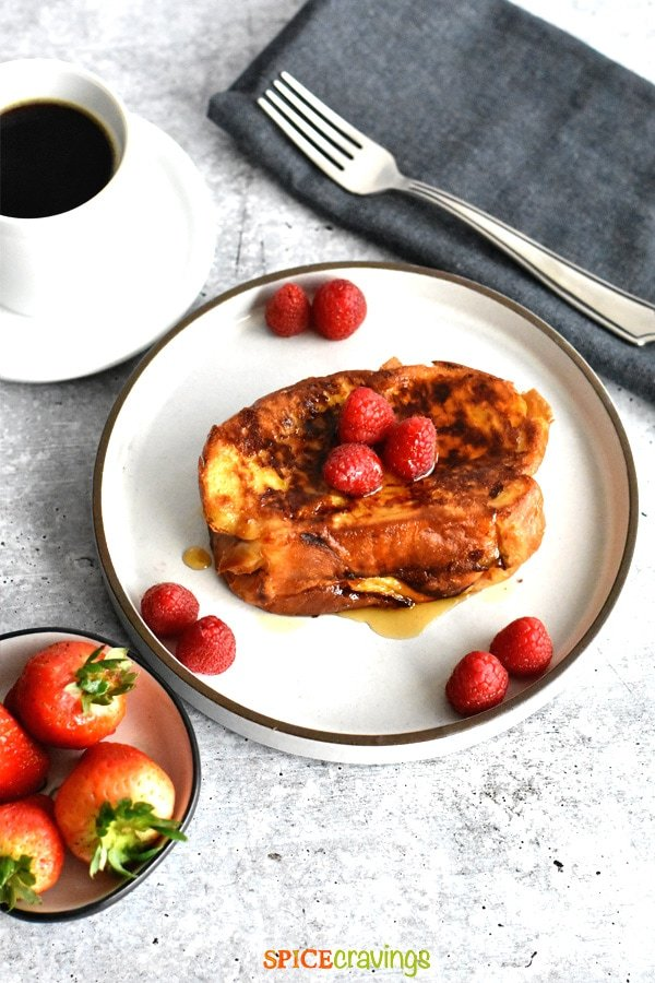 french toast stuffed with nutella on white plate with fork on blue napkin, coffee and strawberries in bowl