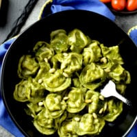 basil pesto pasta in black bowl with fork on blue kitchen towel with grape tomatoes in a bowl