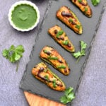 baked samosa stuffed jalapeno poppers on charcoal board with cilantro and tamarind chutney in two white bowls