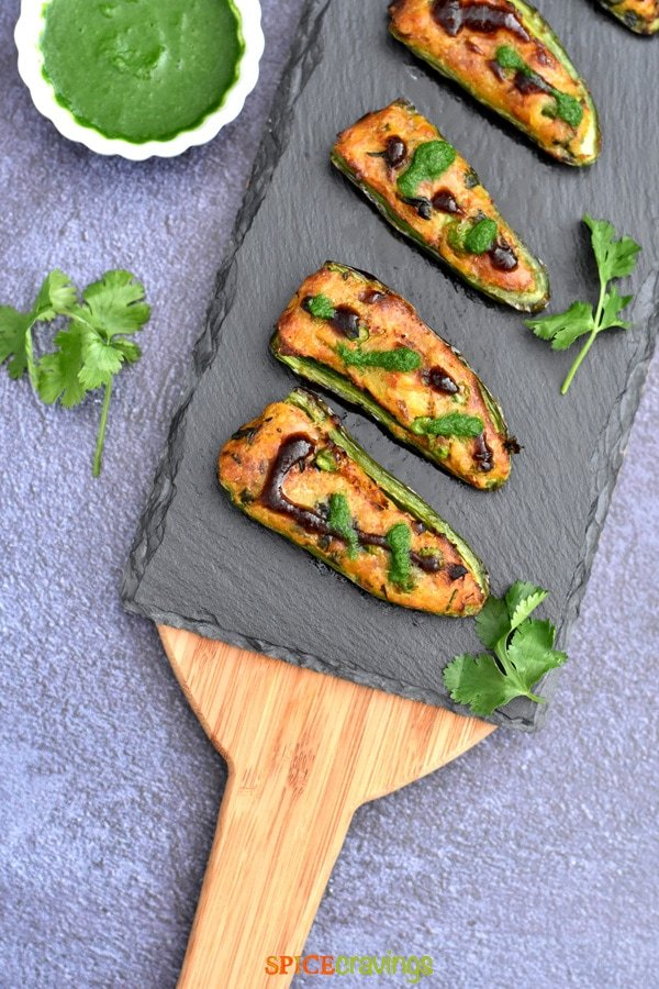 easy samosa stuffed jalapeno peppers on charcoal board with cilantro chutney in small white bowl