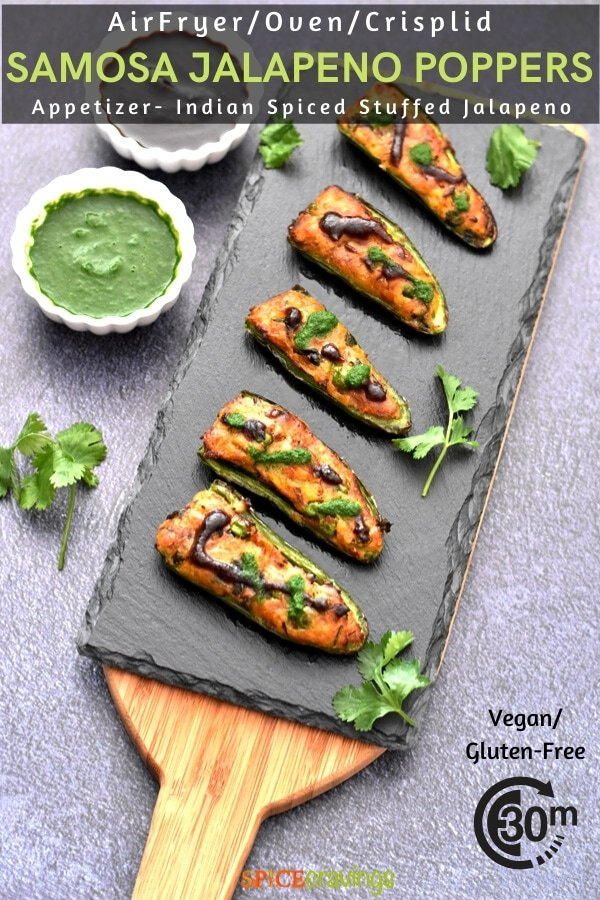 samosa stuffed jalapeno poppers on a charcoal board with cilantro and tamarind chutneys in white bowls