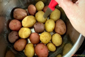 inserting a knife in cooked potatoes