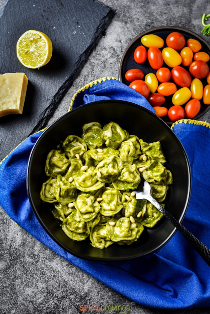 Bowl of pesto tortellini with tomatoes, block of cheese and lime