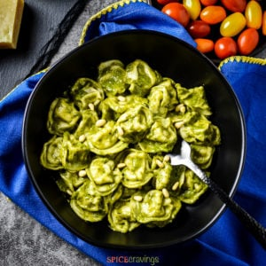 Bowl of pesto tortellini with a side of cherry tomatoes
