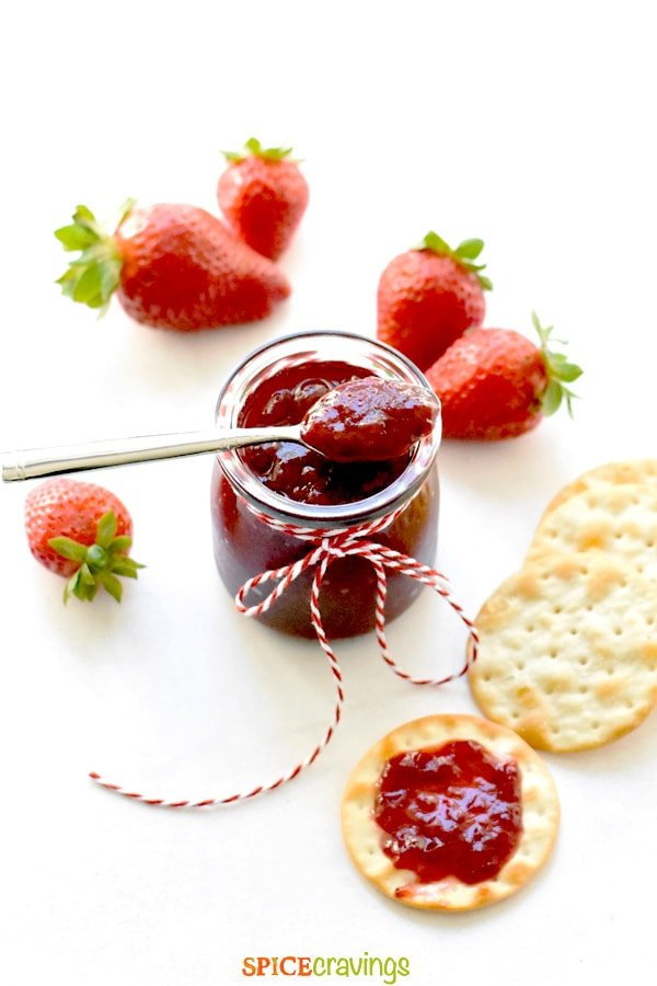 easy strawberry jam in glass jar with silver spoon and fresh strawberries