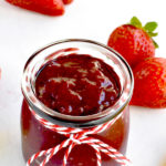 strawberry preserves in glass jar with fresh strawberries