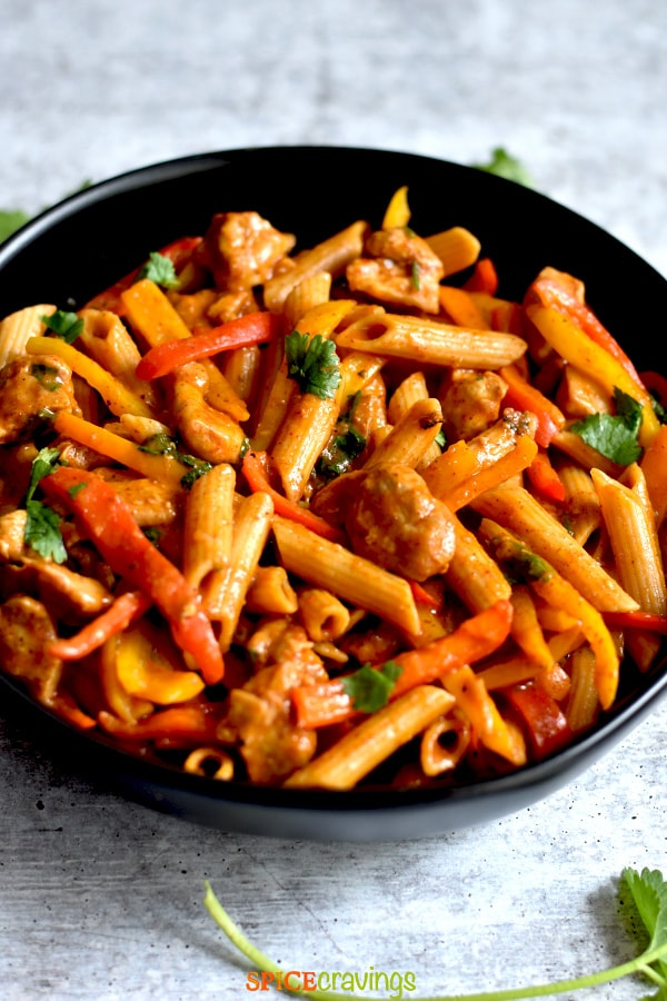 creamy chicken pasta with fajita vegetables in black bowl