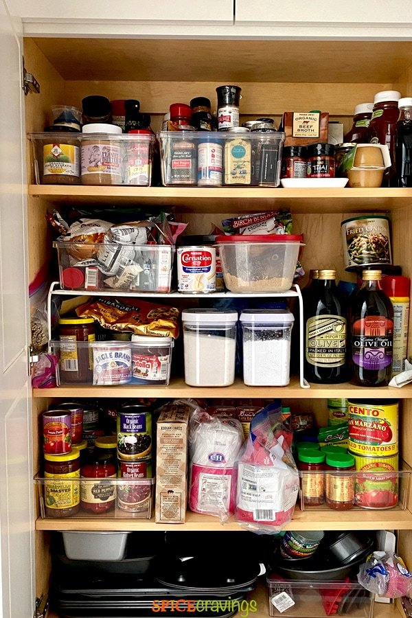 sugar, flour, spices, oil and beans stocked in a pantry