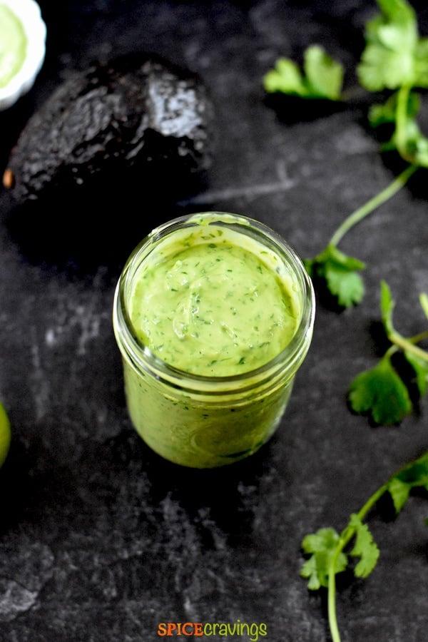 creamy avocado salad dressing recipe in small mason jar with avocado