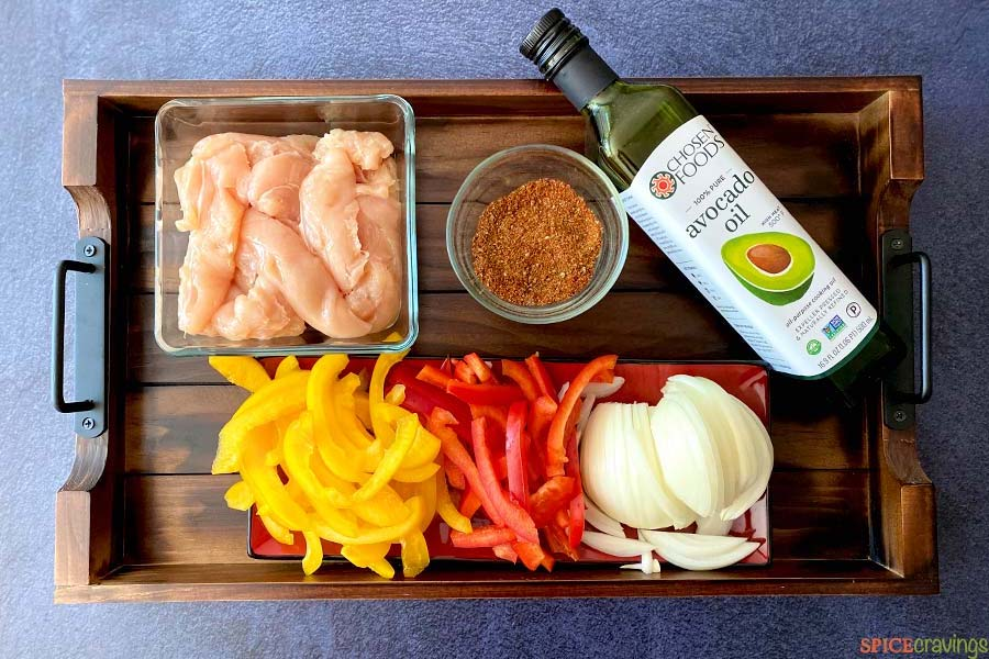 chicke tenders, spice mix, avocado oil, sliced peppers and onions on wooden board