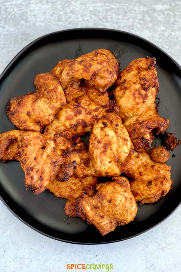 tender middle eastern chicken thighs on black plate